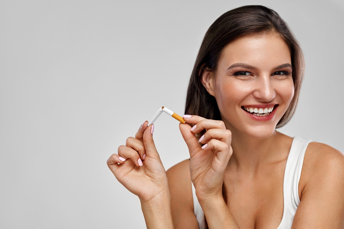 Quit Smoking Cigarettes. Portrait Of Beautiful Smiling Woman Quitting Smoking By Breaking Cigarette. Closeup Of Happy Girl Holding Broken Cigarette In Hands. Health Care Concept. High Resolution