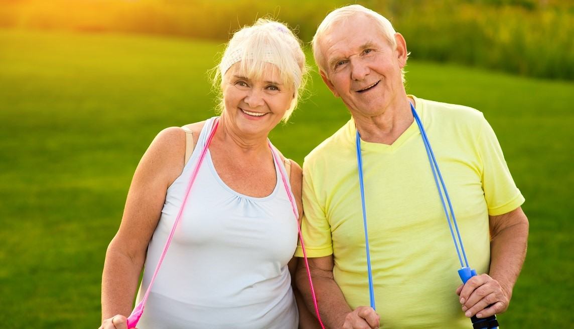 Couple with skipping ropes outdoors. Smiling senior man and woman. Sport unites people. Don't quit trainings.